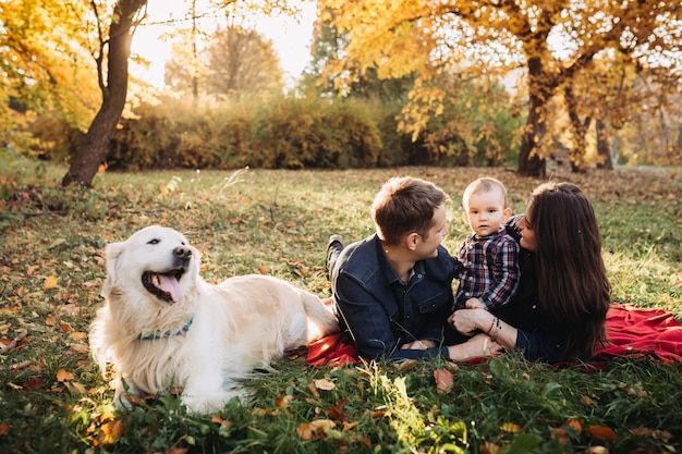 Famiglia con un bambino e un golden retriever in un parco di autunno