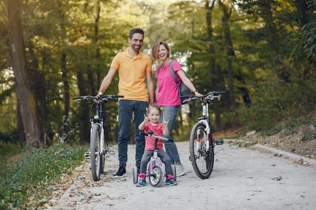 Famiglia con una bicicletta in un parco estivo