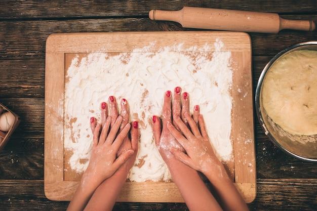 Famiglia cucina torte fatte in casa, le mani della mamma e della figlia nella farina su un tavolo.