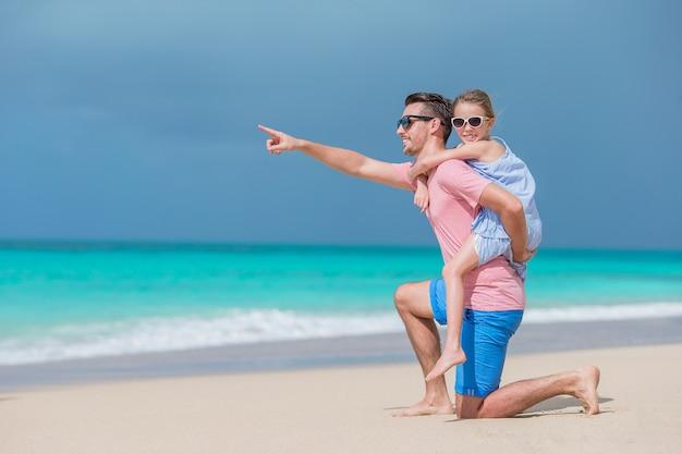 Famiglia del padre e bambina sportiva divertendosi sulla spiaggia