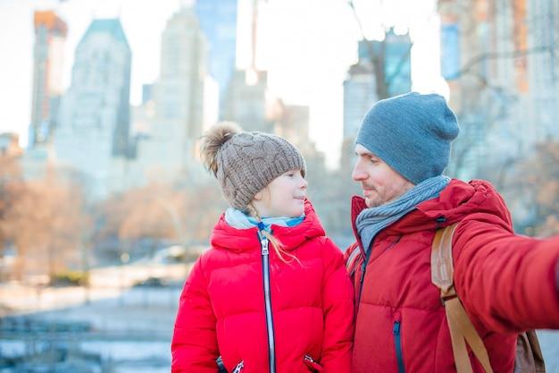 Famiglia del papà e del bambino che prendono la foto del selfie in central park a new york city