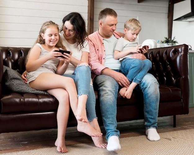 Famiglia della foto a figura intera che si siede sullo strato