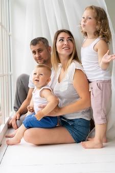 Famiglia della foto a figura intera che sta insieme vicino alla finestra
