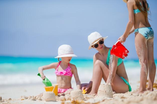 Famiglia della mamma e dei bambini che fanno il castello di sabbia alla spiaggia tropicale