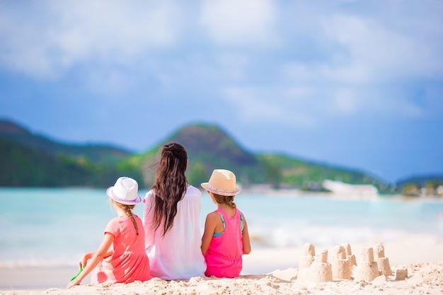 Famiglia della mamma e dei bambini con il castello di sabbia alla spiaggia tropicale