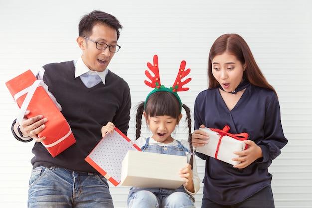 Famiglia di buon natale e vacanze allegre. la madre e il padre sorprendono con i bambini. figlia e genitore che tengono regalo attuale al salone bianco.