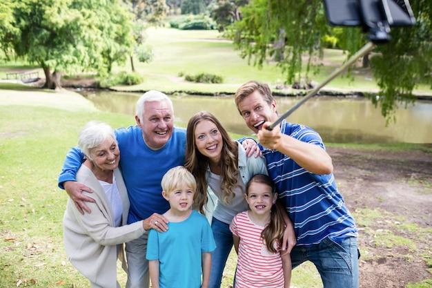 Famiglia di diverse generazioni che prende un selfie con il bastone del selfie
