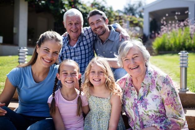Famiglia di diverse generazioni che si siede nel giardino