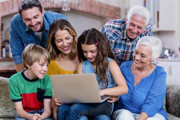 Famiglia di diverse generazioni che si siede sul sofà e che per mezzo del computer portatile