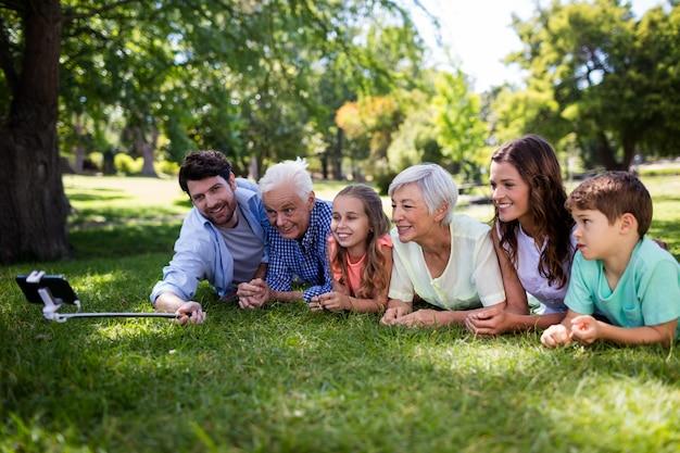 Famiglia di diverse generazioni che si trova sull'erba e che prende un selfie