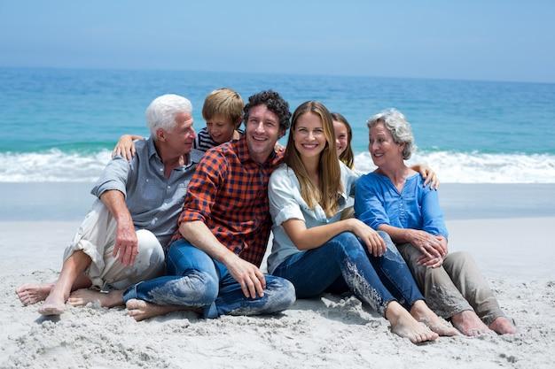 Famiglia di diverse generazioni che sorride rilassandosi alla riva di mare