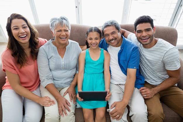 Famiglia di diverse generazioni che utilizza compressa digitale nel salone a casa