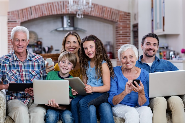 Famiglia di diverse generazioni che utilizza un laptop, un tablet e un telefono
