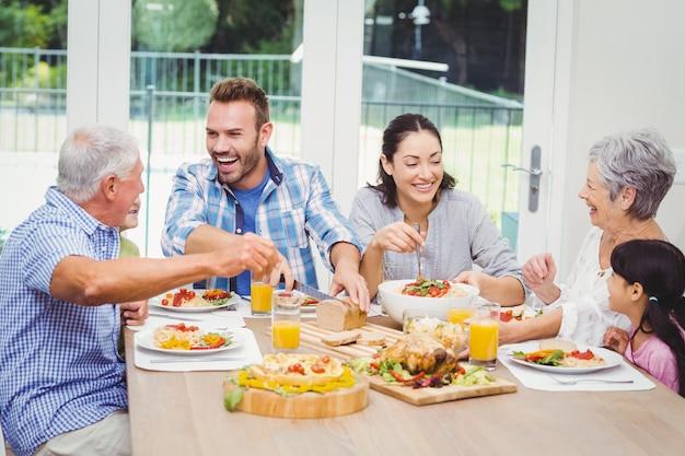 Famiglia di diverse generazioni felice che mangia cibo al tavolo da pranzo