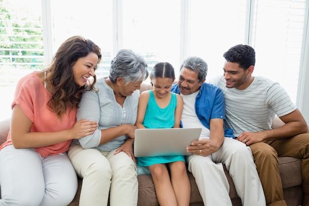 Famiglia di diverse generazioni felice che utilizza computer portatile nel salone