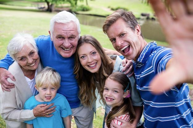 Famiglia di diverse generazioni in posa per un selfie nel parco