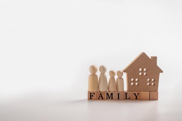 Famiglia di figure di legno che sta accanto ad una casa di legno su un cubo di legno che scrive la parola famiglia.