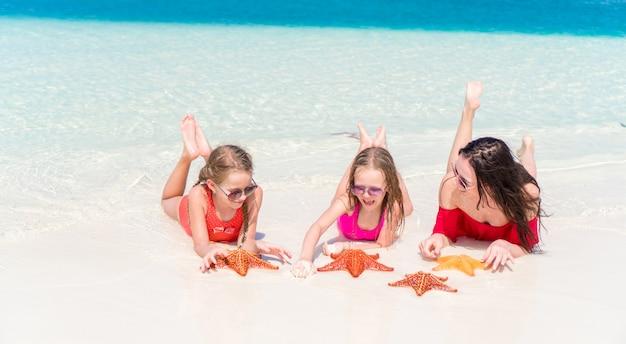 Famiglia di mamma e bambini in spiaggia tropicale
