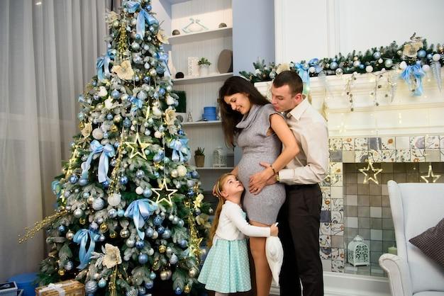 Famiglia di natale che si leva in piedi vicino all'albero di natale