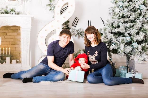 Famiglia di natale con regali di apertura del bambino. genitori e bambino sorridenti felici a casa che celebrano nuovo anno
