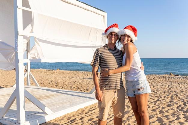 Famiglia di natale coppia marito e moglie fanno selfie sul telefono. uomo e donna che indossano cappelli di babbo natale sorridendo, ridendo per celebrare il nuovo anno sulla spiaggia sabbiosa