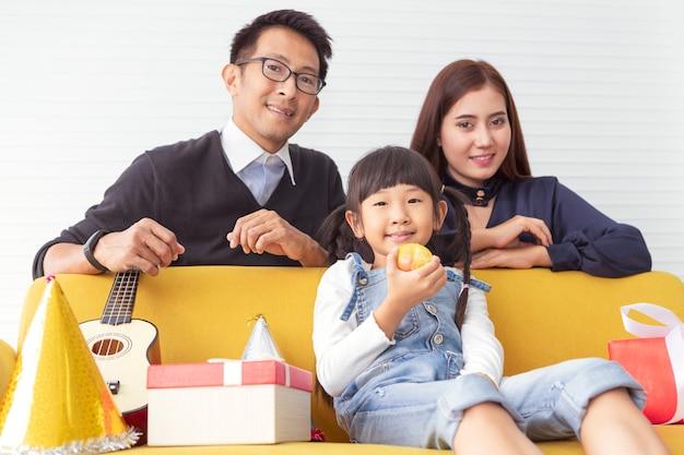 Famiglia di natale e goditi le vacanze. il bambino mangia la mela. la madre e il padre sorprendono il regalo attuale con i bambini al salone bianco.