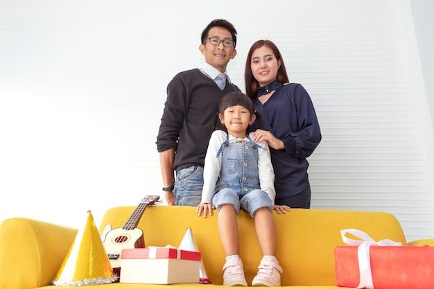 Famiglia di natale e vacanze allegre. la madre, il padre ed i bambini si avvicinano al regalo attuale al salone bianco.