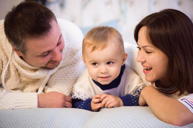 Famiglia di natale. felice mamma, papà e figlio piccolo sdraiato sul letto