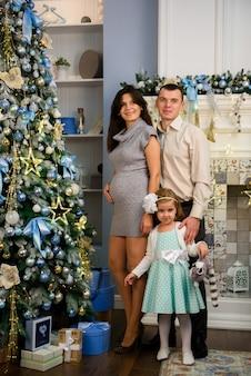 Famiglia di natale. mamma e papà e la loro figlioletta insieme a casa.