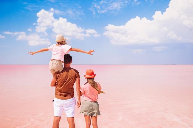 Famiglia di padre e bambine su un lago salato rosa in una giornata di sole estivo. esplorare la natura, i viaggi, le vacanze in famiglia.