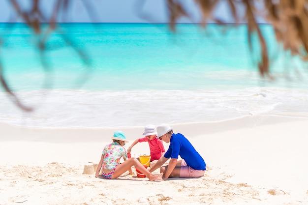Famiglia di papà e bambini che fanno il castello di sabbia in spiaggia tropicale