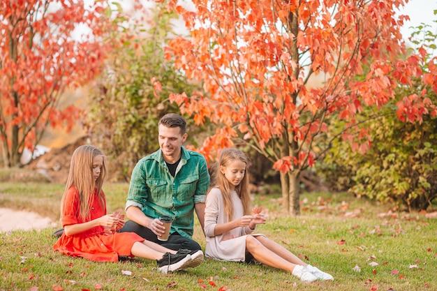 Famiglia di papà e bambini in bella giornata d'autunno nel parco