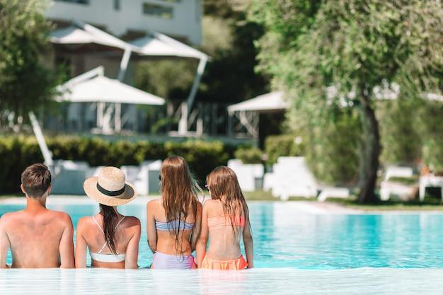 Famiglia di quattro felice nella piscina all'aperto