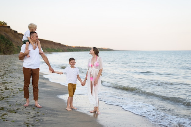 Famiglia di quattro persone che cammina lungo la riva del mare. genitori e due figli. felice famiglia amichevole