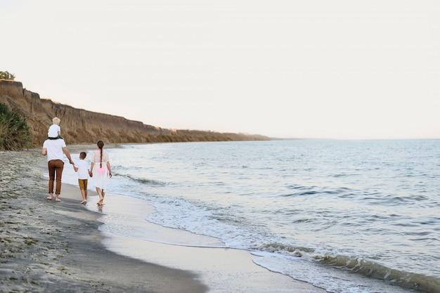 Famiglia di quattro persone che cammina lungo la riva del mare. genitori e due figli. vista posteriore