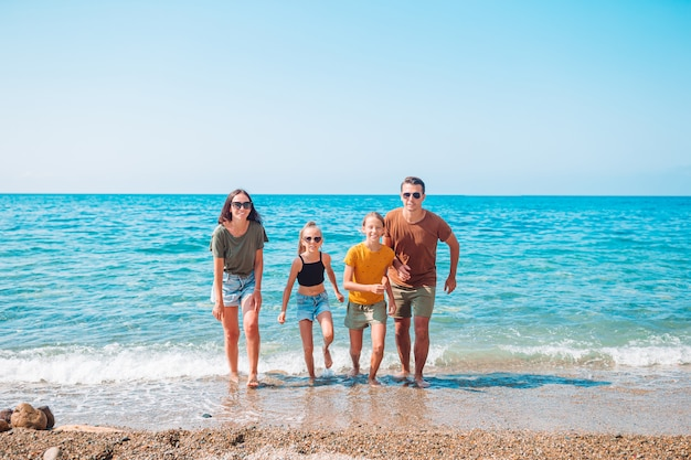 Famiglia di quattro persone che si divertono insieme sulla spiaggia