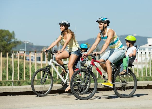 Famiglia di quattro persone che viaggiano in bicicletta