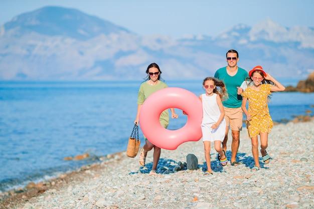Famiglia di quattro persone sulla spiaggia divertendosi. bambini e genitori corrono in riva al mare