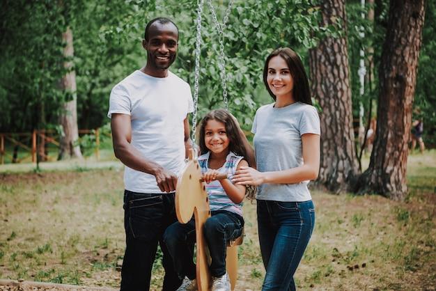 Famiglia di razza mista in park kid girl su horse swing