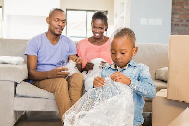 Famiglia di scartare le cose nella nuova casa in salotto