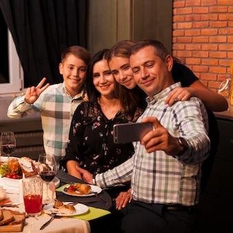 Famiglia di smiley del colpo medio che prende selfie