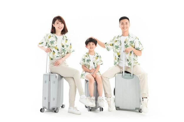 Famiglia di tre persone che viaggiano seduti sulla valigia