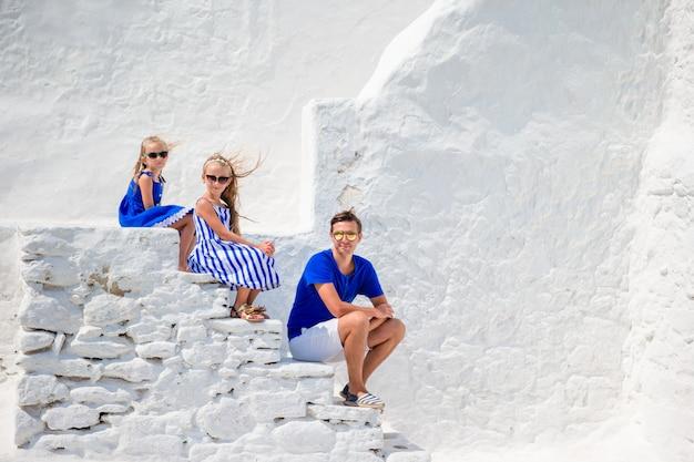 Famiglia di tre persone sulle scale della chiesa paraportiani sull'isola di mykonos, in grecia