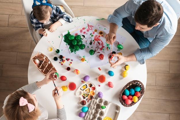 Famiglia di vista superiore che dipinge insieme le uova di pasqua