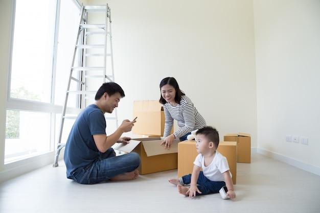 Famiglia disimballo scatole nella nuova casa il giorno commovente