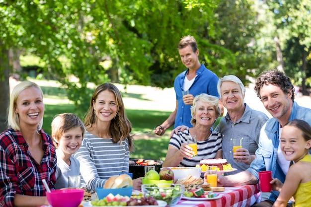 Famiglia e amici che hanno un picnic con barbecue