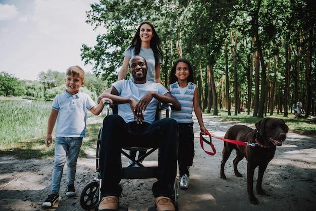 Famiglia e cane all'aperto disabile dell'uomo felice della gente