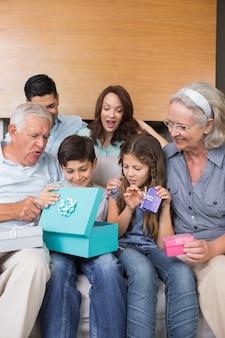 Famiglia estesa che si siede sul sofà con i contenitori di regalo in salone