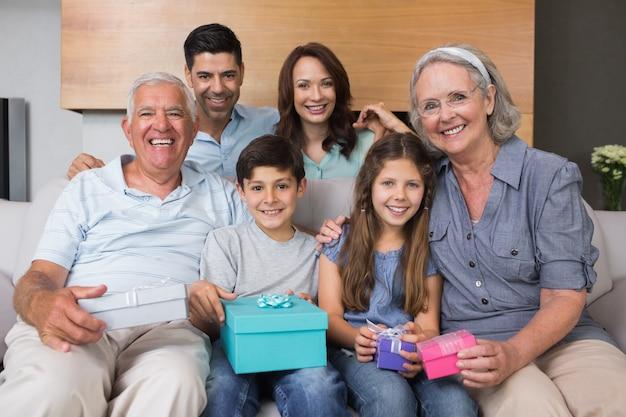 Famiglia estesa sul divano con scatole regalo in salotto