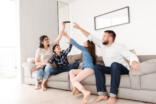 Famiglia europea con figlio e figlia seduti sul divano insieme nel soggiorno di casa e cercando di afferrare lo smartphone dalla donna